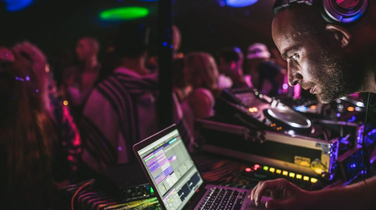 Male DJ looking at laptop screen whilst playing in front of a Noisily Festival 2018 stage