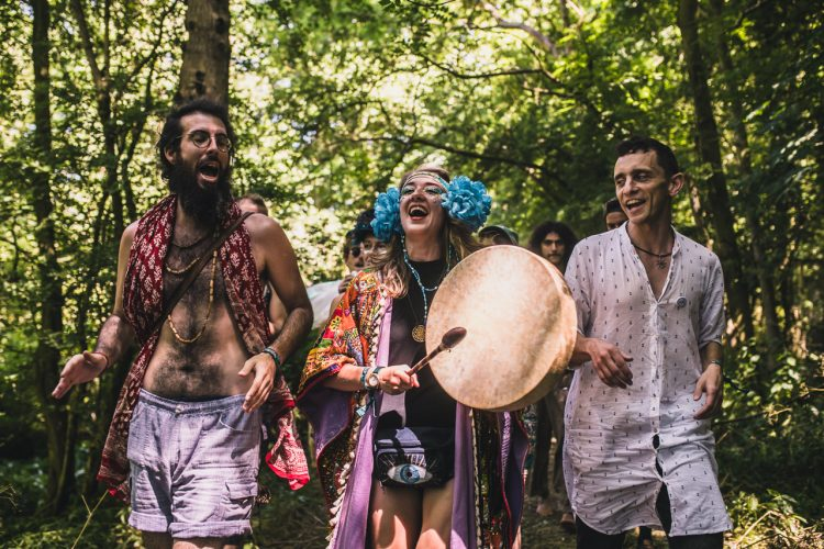 female performer banging drum whilst walking through coney woods at Noisily Festival 2019
