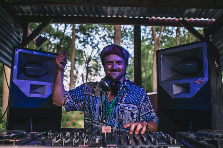 male DJ in vintage hippie shirt pointing into the sky during Noisily Festival 2018