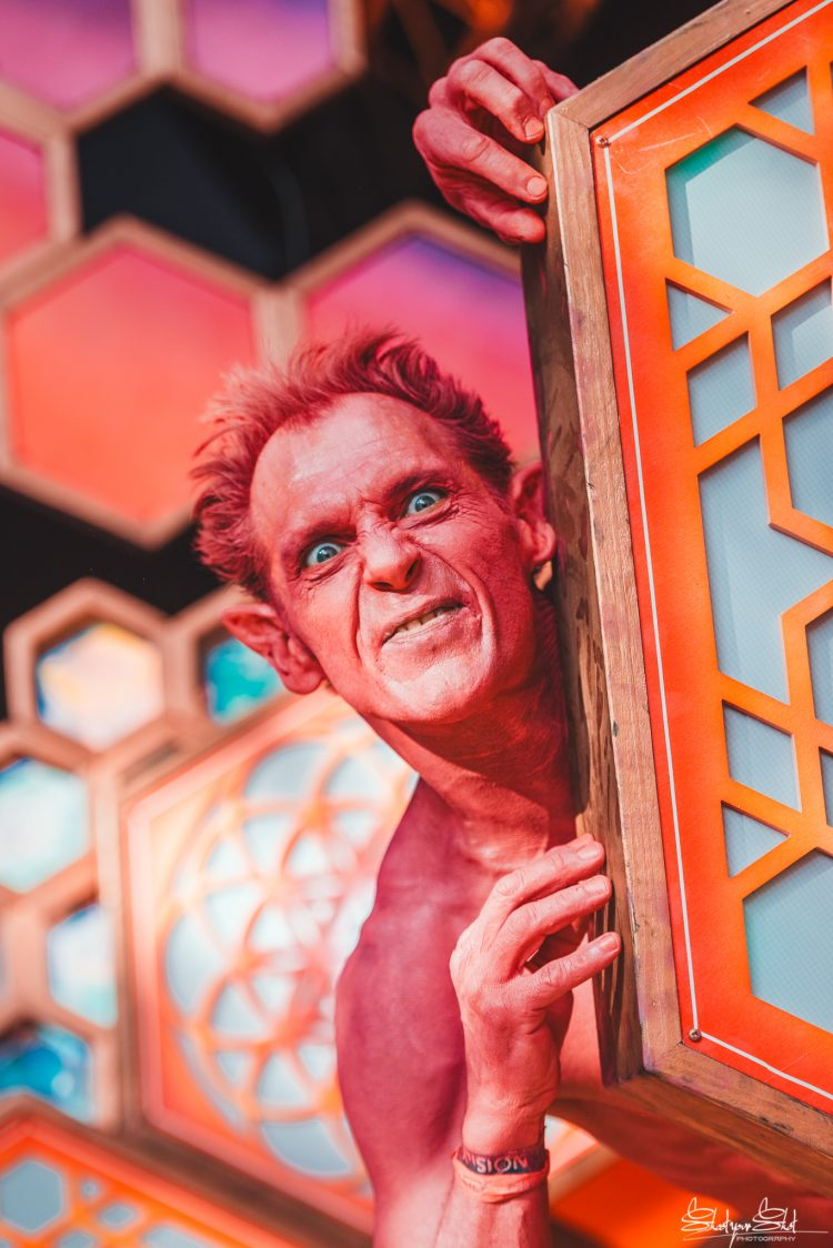 man dressed as pink goblin peeking from behind the liquid stage during Noisily festival 2018