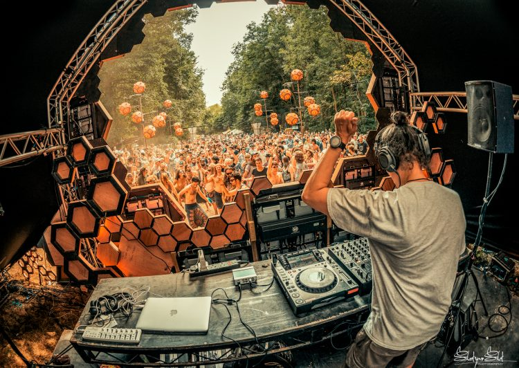 Male DJ plays psytrance in front of crowd on the liquid stage during Noisily Festival 2018