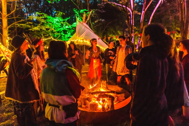 Noisily Festival 2019 attendees standing around a fire at night