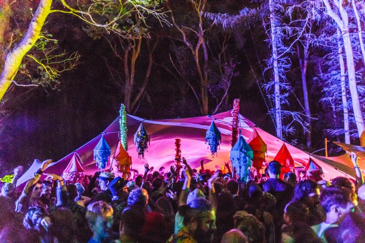 crowd of Noisily Festival-goers standing outside a small music stage at