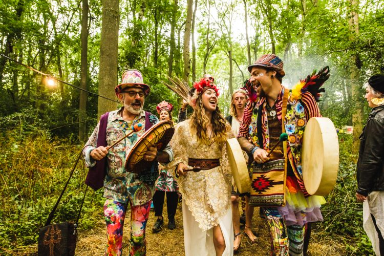 group of performers in fancy dress marching through the woods of Noisily Festival 2019
