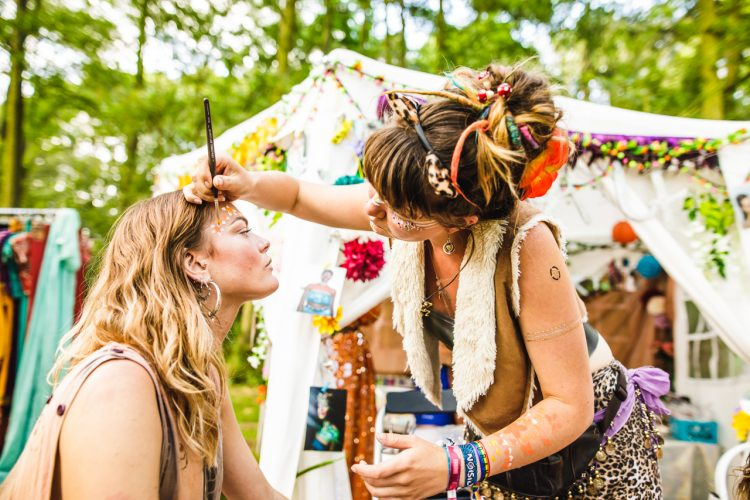 young woman painting woman's face outside Mind Body Soul tent