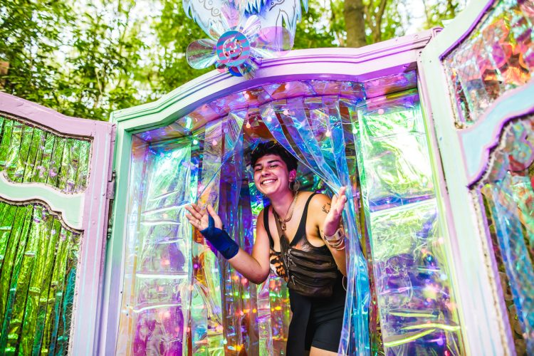 woman walking out of art installation smiling at Noisily Festival 2019