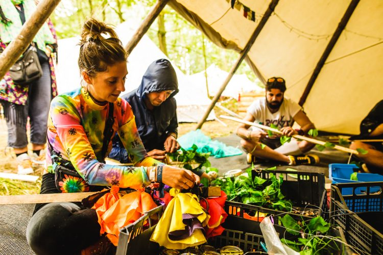 three festival attendees sitting inside a Mind Body Soul tent crafting decorations