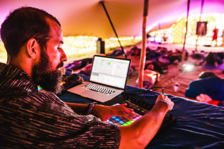 man pressing buttons on a beat pad inside a Mind Body Soul tent