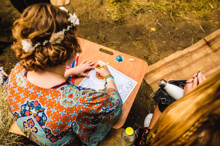 lady with flowers in hair colouring in some paper at Noisily Festival 2019