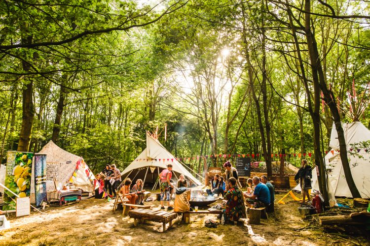people sat outside tents in the woods of Noisily Festival 2019