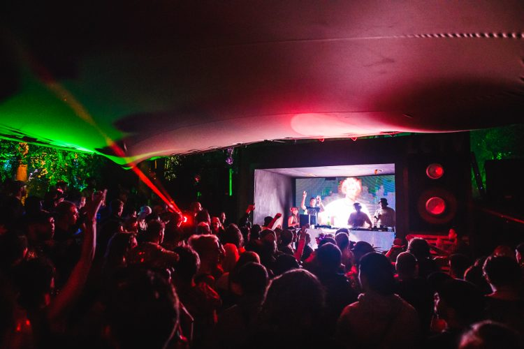 crowd of festival-goers watching a DJ perform inside a tent at Noisily Festival 2019