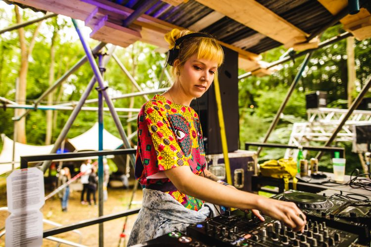 female DJ turning knobs inside a Noisily Festival 2019 music stage