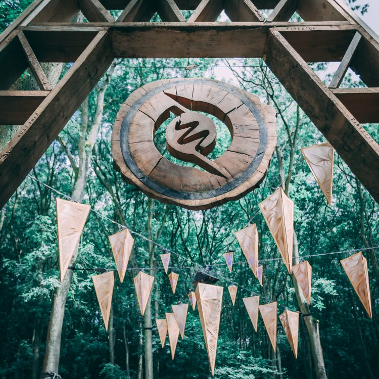 Wooden Noisily Festival 2019 sign hanging in forest canopy with lights
