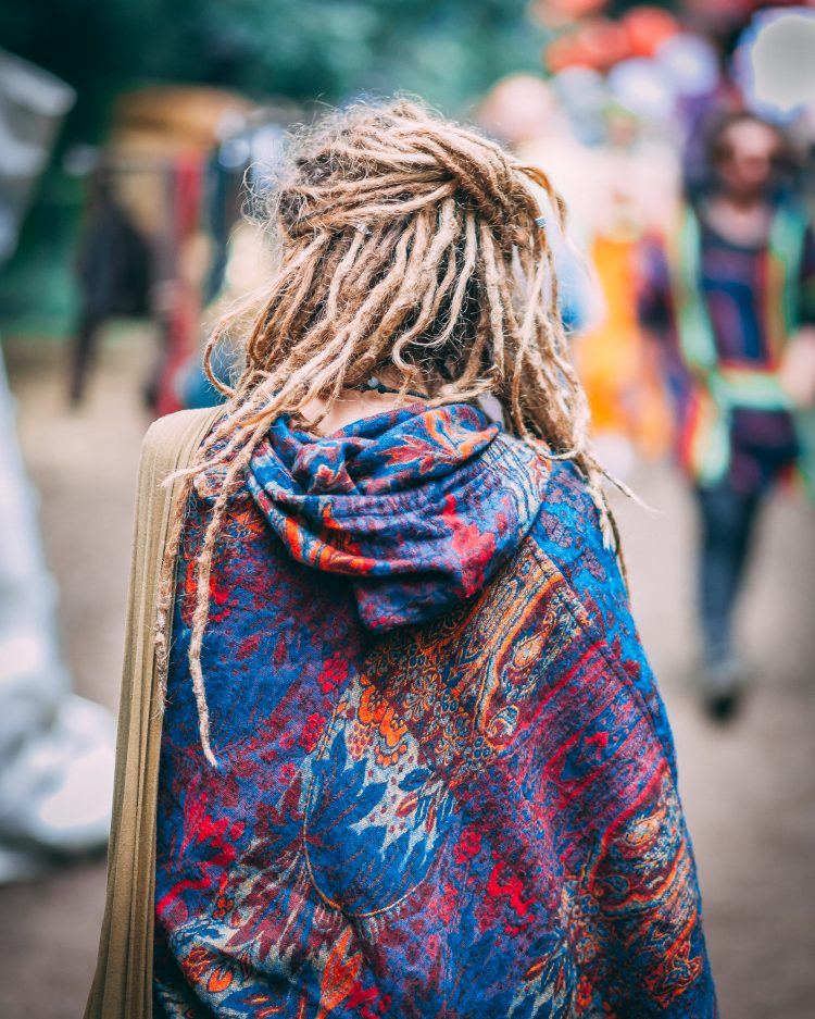 Woman with dreadlocks and colourful hoodie walking away from camera at Noisily Festival 2019