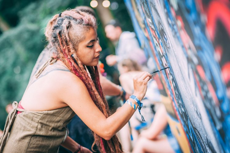 Woman with dreadlocks painting a mural at Noisily Festival 2019