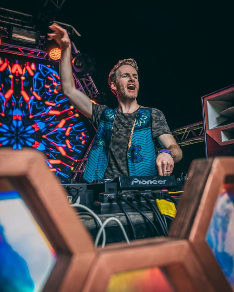 Male DJ pointing into the air and playing psytrance on the Noisily Festival 2019 Liquid stage