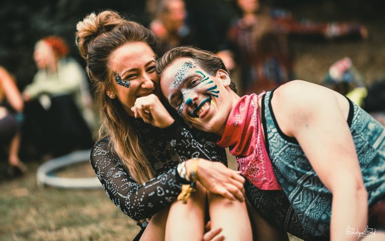 Man and woman in face paint sitting on the floor and laughing during Noisily Festival 2019