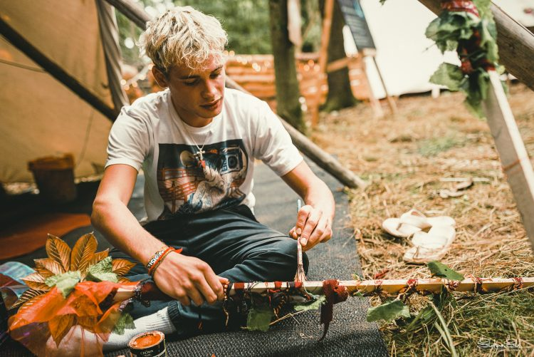 Young man sitting on the ground decorating a stick during Noisily Festival 2019
