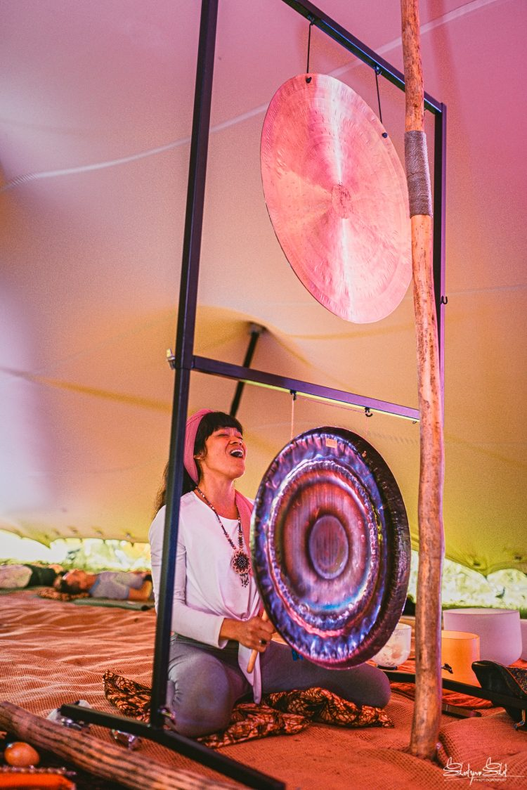 Woman with bandana singing and hitting a gong inside a Noisily Festival 2019 tent