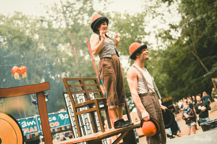 Male and female performer wearing several hats standing on a stage at Noisily Festival 2019