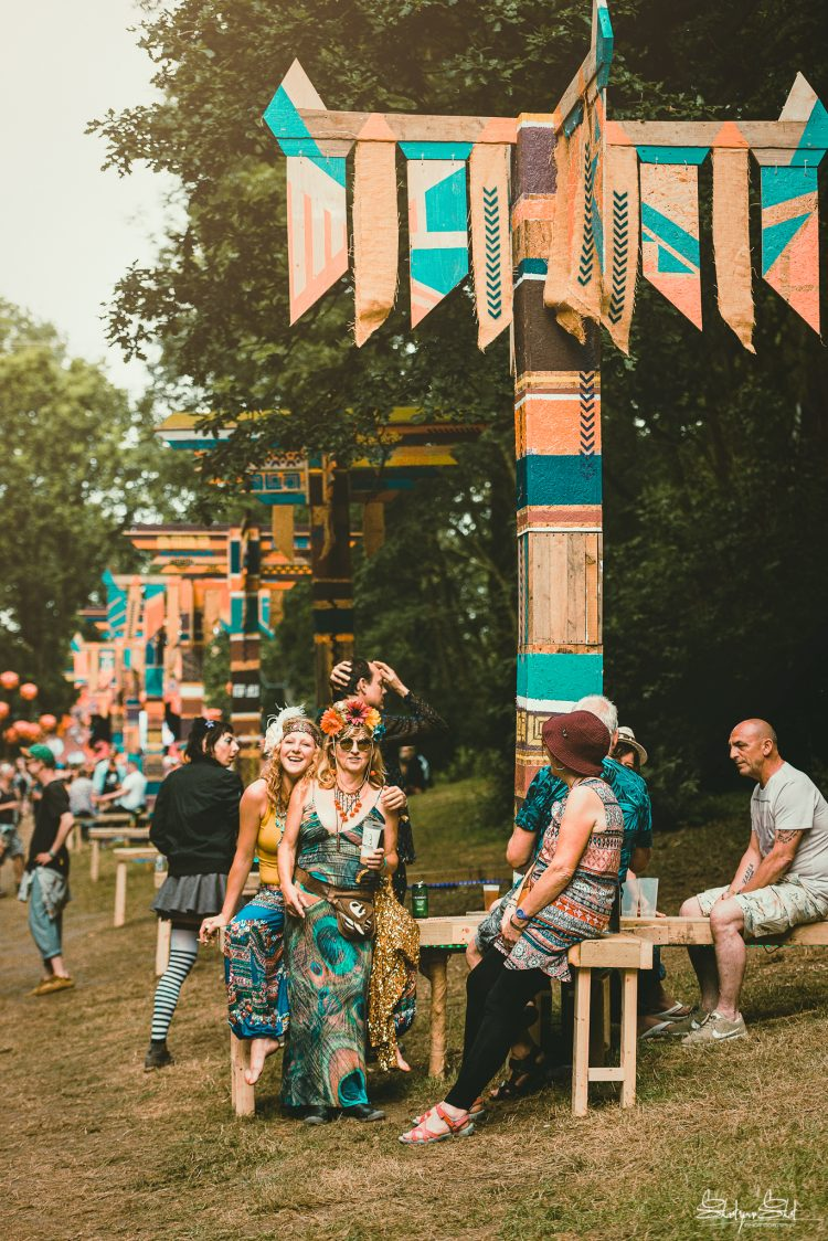 group of Noisily Festival 2019 attendees sitting under a totem pole