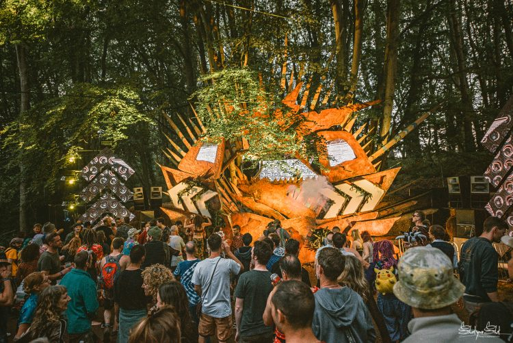 Crowd of Noisily festival attendees watching the Treehouse stage in the woods