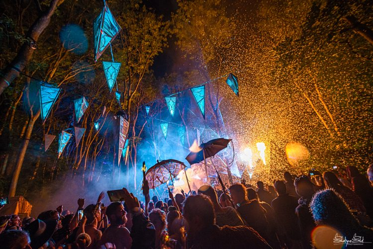 two people holding umbrellas above the Noisily Festival crowd in front of a stage