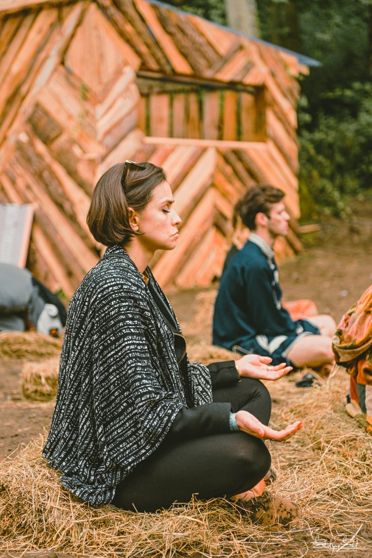 woman sitting with her legs crossed on the grass and meditating at Noisily Festival 2019