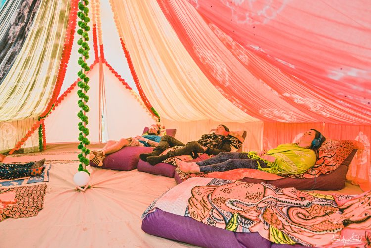 three people relaxing with headphones inside a Mind Body Soul tent at Noisily festival 2019