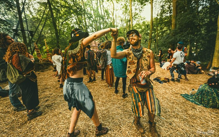 two male festival attendees holding hands and dancing in the Noisily Festival 2019 forest
