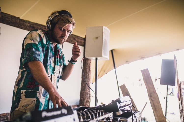 male DJ in colourful shirt concentrating on playing during Noisily Festival 2018