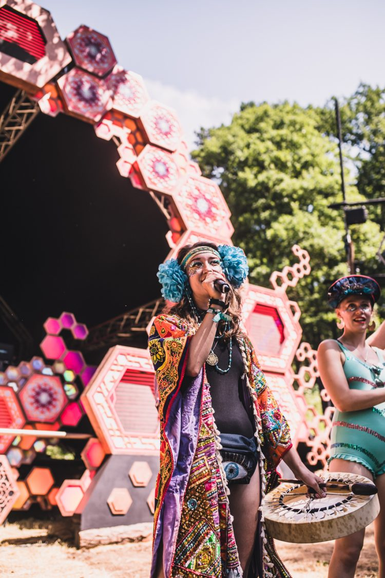 female performer in fancy dress speaks into microphone in front of psytrance liquid stage during Noisily Festival 2018