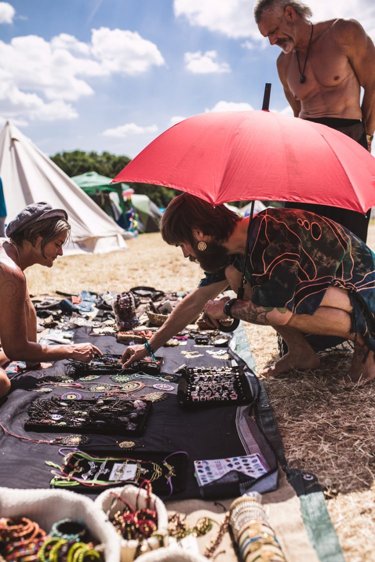 man with red umbrella pointing at shop products during Noisily Festival 2018