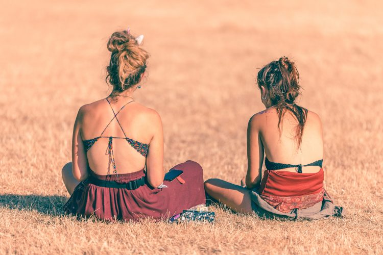 two young women in bikinis sitting on the grass at Noisily festival 2018