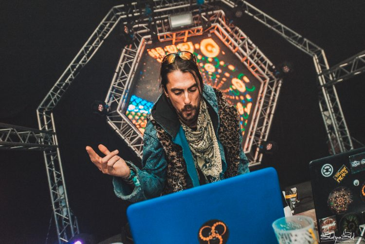 male DJ dressed in robes looking at laptop and playing psytrance at liquid stage during Noisily Festival 2018