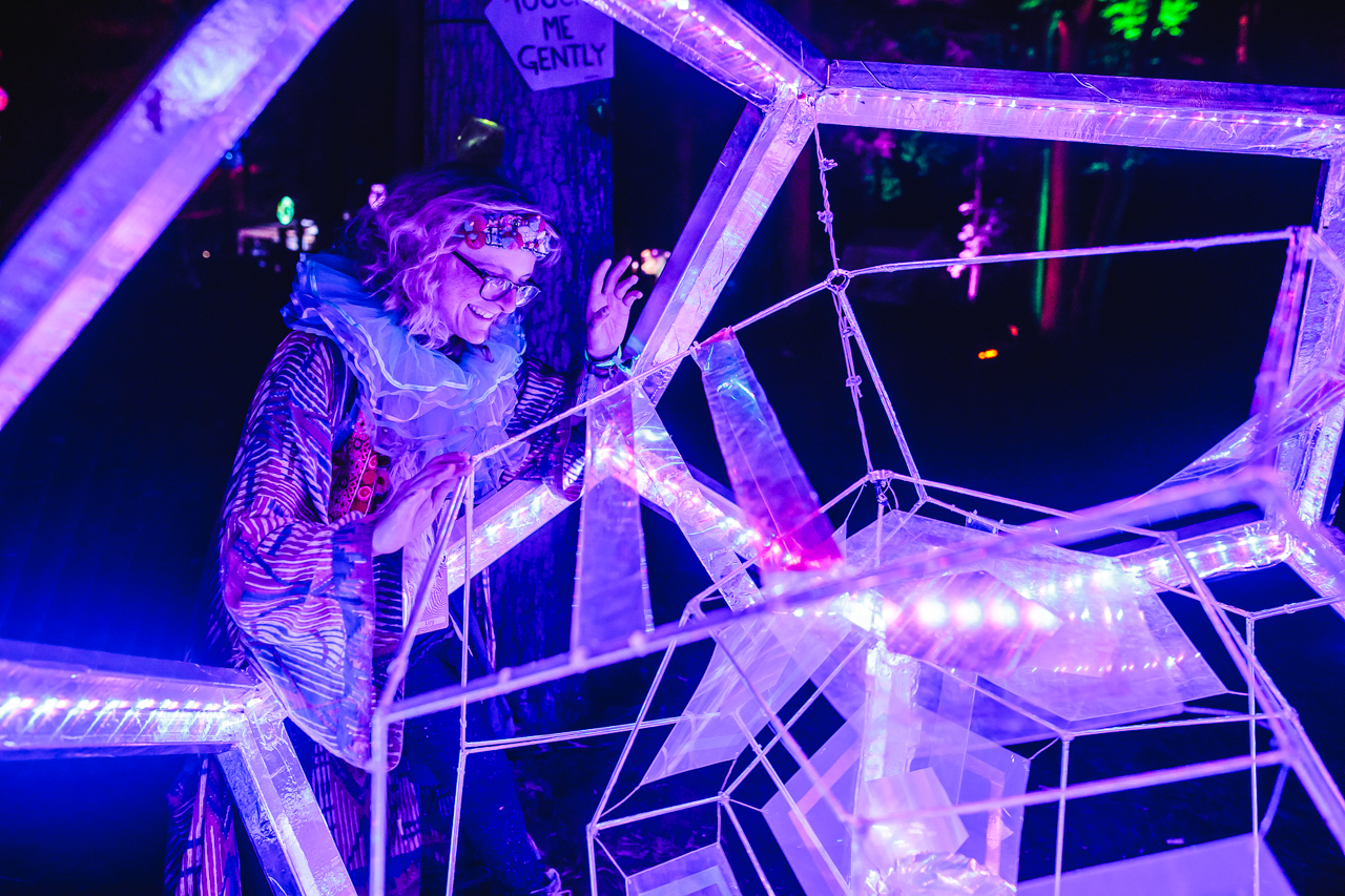 Woman in fancy dress looking at orb art installation at Noisily Festival