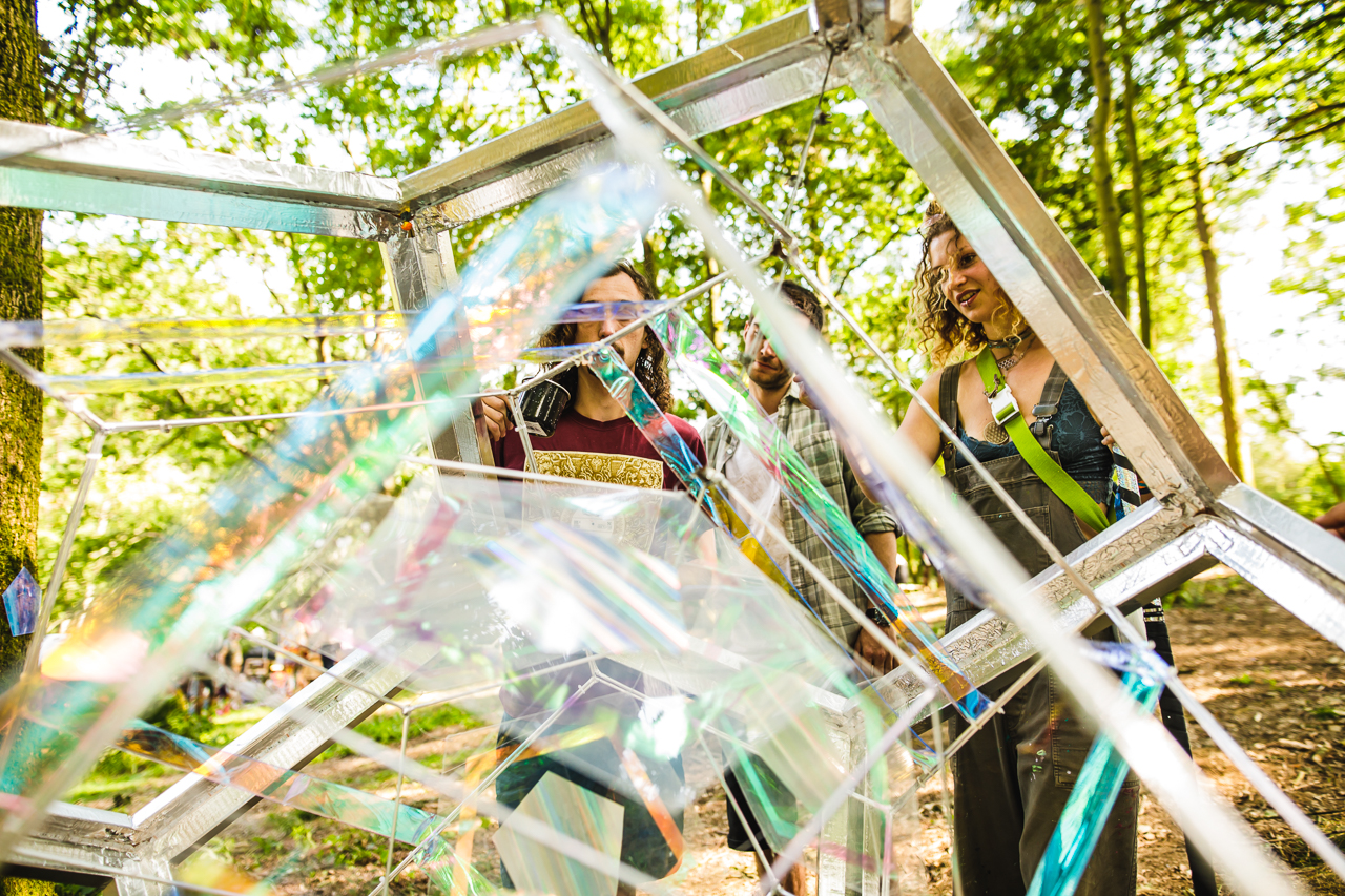 Festival goers looking at orb art installation at Noisily Festival in the Woods.